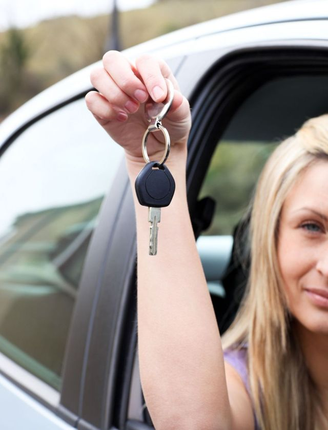 Woman holding the key to excellent driving instruction in in Oxford, OH