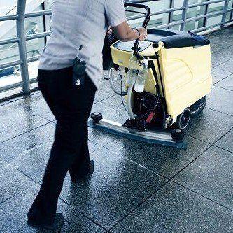 addetto pulisce pavimenti con macchinario professionale
