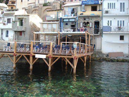 Un pontile in legno con dei tavoli sul mare