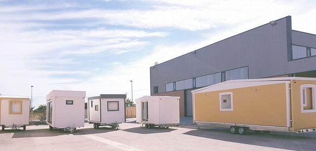 dei rimorchi mobili di color giallo e bianco all'interno di un parcheggio di un'azienda