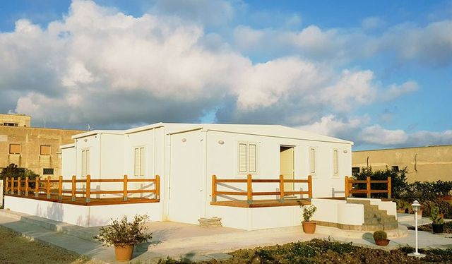 una costruzione di color bianco con un terrazzino e dei parapetto in legno e dietro vista del cielo blu e di altre costruzioni