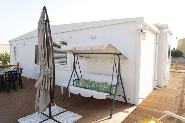 un terrazzino di legno con un dondolo rivestito di bianco con cuscini verdi a fiori rosa,un ombrellone chiuso, un tavolo bianco di plastica e dietro una costruzione di color bianco