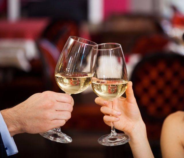 due mani con dei bicchieri durante un brindisi