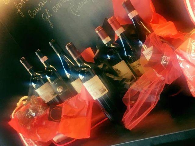delle bottiglie di vino con dei fiocchi di velo rosso