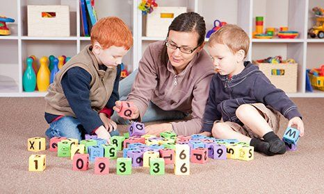 children playing block game with teachers