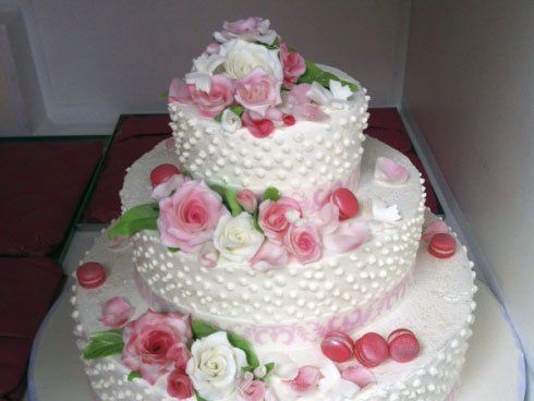 Torta di tre appartamenti in crema con guarnizioni di foglie verdi di zucchero,rose rosse e bianche di zucchero anche e macarroni rosa di crema