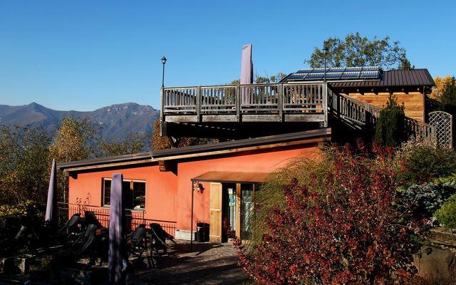 uno stabile con terrazza e vista delle montagne e accanto un lago