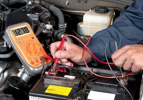 Tecnica verifica le connessioni di una batteria di un auto