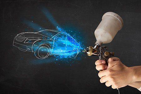 una mano con una pistola da verniciatura e il disegno di un'auto
