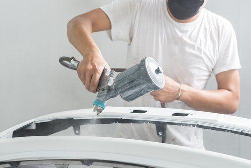 Persona dipinge macchina a spruzzo