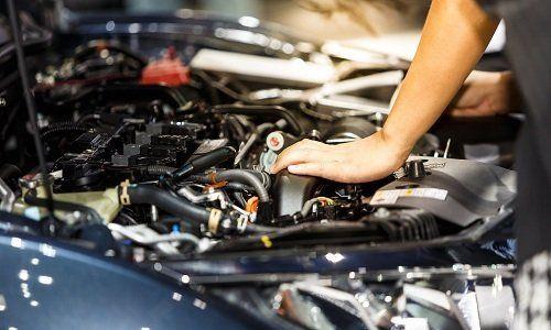 le mani di un meccanico mentre fanno la revisione del motore