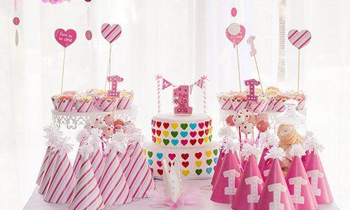 dei cappellini rosa e bianchi da festa e una torta