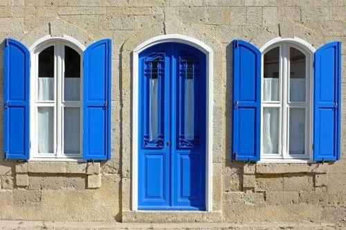 vista di una casa con delle finestre e delle porte finestre con delle persiane blu
