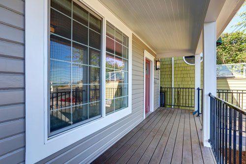 vista dall'esterno di una veranda in legno e delle finestre in vetro e rifiniture bianche