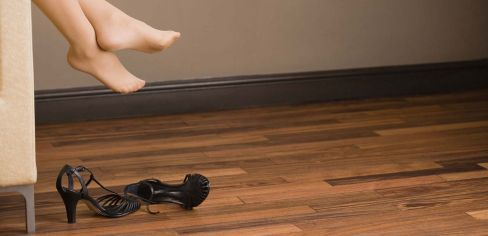 lady taking off shoes on a wooden floor