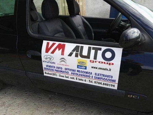 insegna VM AUTO attaccata al lato di una macchina