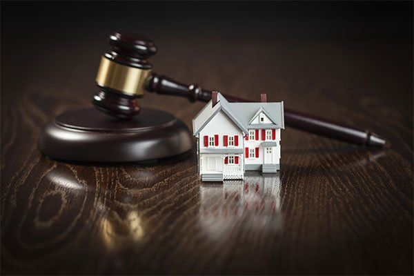 Gavel and small model house on wooden table