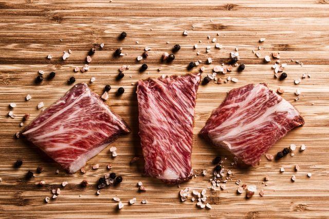 Tre pezzi di carne su un tavolo di legno