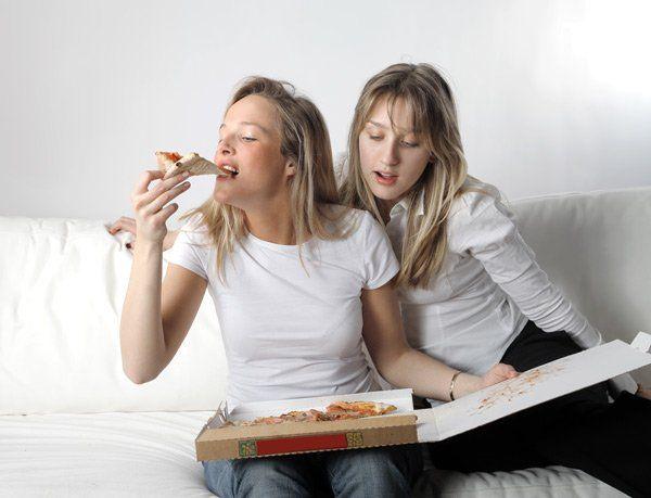 due donne che si dividono una pizza da asporto