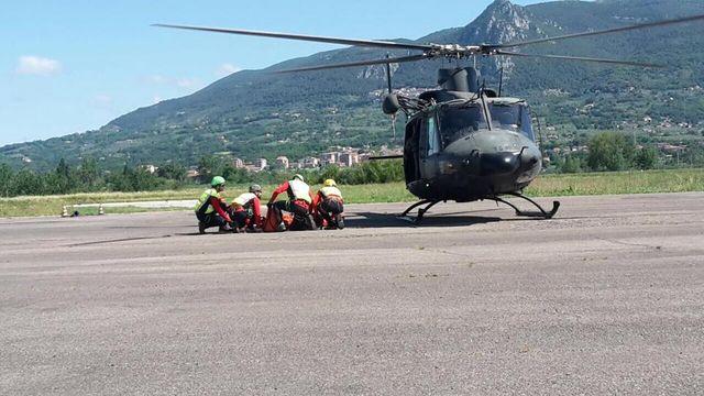 Dei soccorritori e accanto un elicottero nero