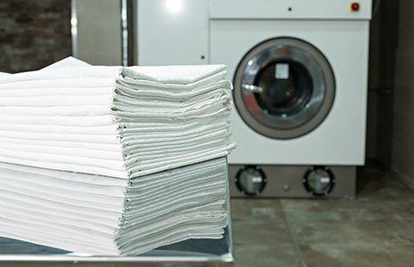 delle lenzuola piegate e una lavatrice