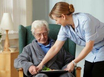 nurse helping a old lady with her food