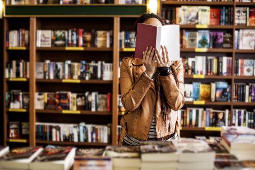 Ragazza che legge un libro in una libreria