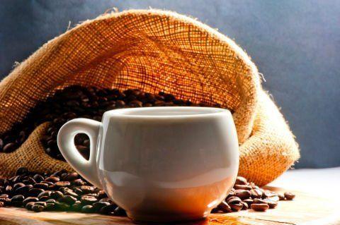 una tazza e un sacco in juta con dei chicchi di caffè'