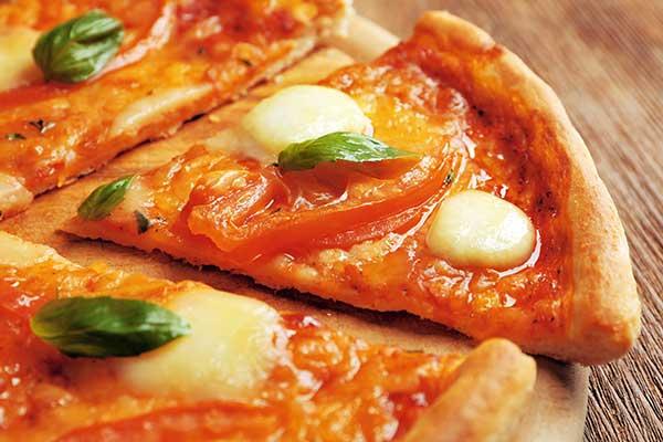 pizza margherita con mozzarella e foglie di basilico tagliata e vista da vicino a Licciana Nardi, MS