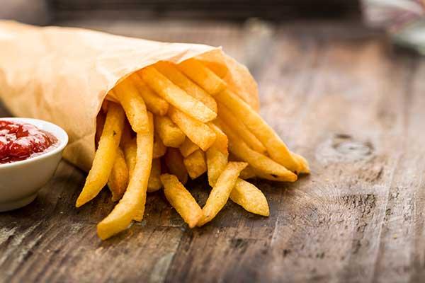 un sacchetto di carta color marrone con dentro delle patatine fritte e accanto una piccola ciotola con del ketchup a Licciana Nardi, MS