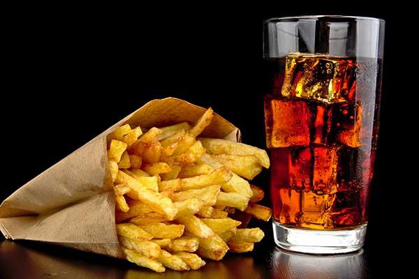 un sacchetto di patatine fritte e accanto un bicchiere di Coca Cola con ghiaccio a Licciana Nardi, MS