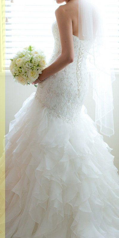 wedding dress and bride holding white bouquet