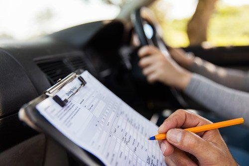 Istruttore di guida scrive appunti su un foglio durante una prova