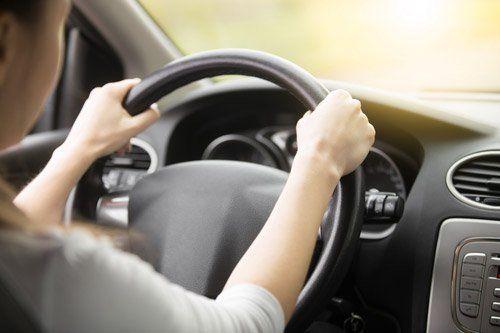 un ragazza al volante di un'auto