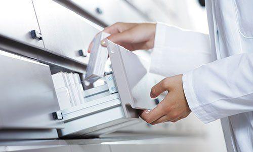 farmacista prende un pacchetto dal cassetto dei farmaci