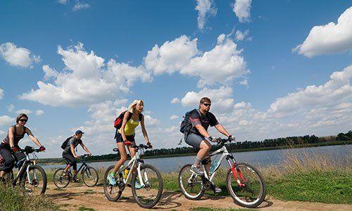 gruppo misto di ciclisti in mountain bike vicino uno specchio d'acqua