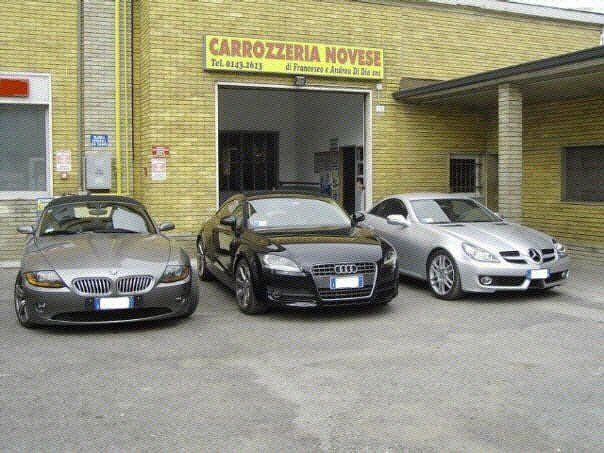 tre auto di lusso di fronte a una carrozzeria