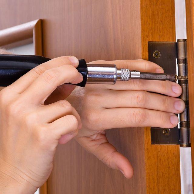 mani avvitano cerniera su una porta con un cacciavite