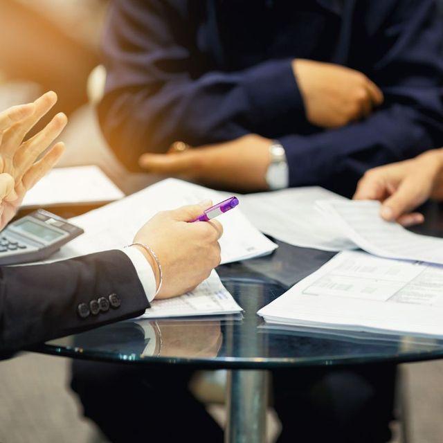 Delle persone sedute a una scrivania con dei documenti