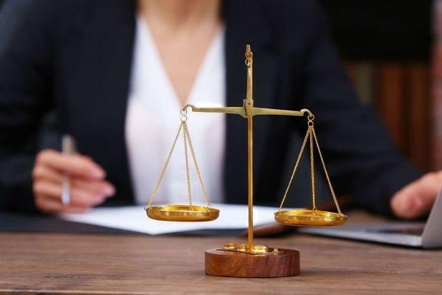 Primo piano della bilancia della giustizia davanti a una donna