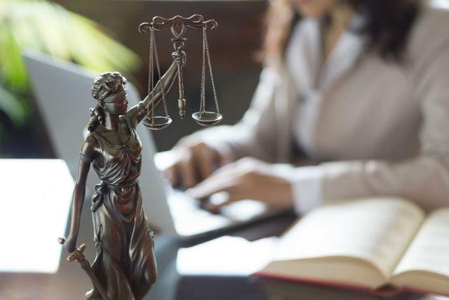 Piccola statua con gli occhi bendati che sostiene la bilancia della giustizia e una spada