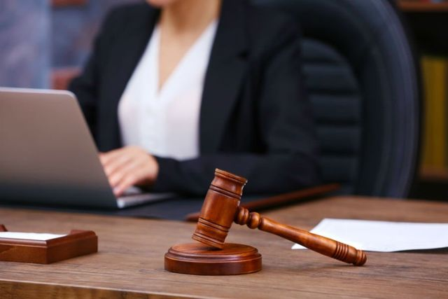 Primo piano del martello della giustizia davanti a una donna che usa un computer