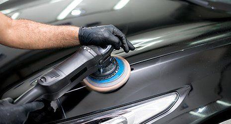 Operaio puliendo un'automobile