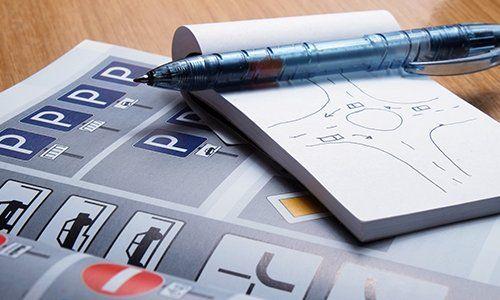 un libro di scuola guida e un blocchetto con una penna