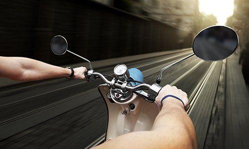 due mani che guidano uno scooter