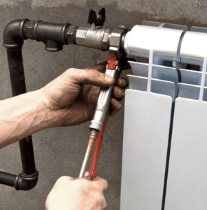 fitting heating pipe to radiator with a spanner