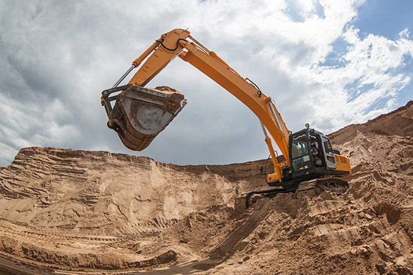 An excavator removing sand from a construction site