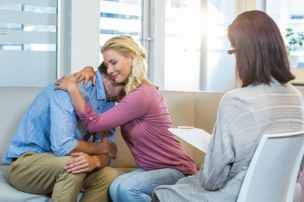 una donna bionda che abbraccia un uomo triste e di fronte una psicologa