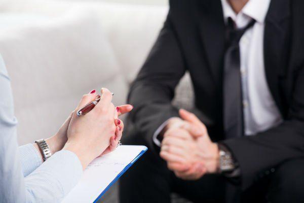 un uomo seduto con un completo nero e di fronte le mani di una donna con una penna