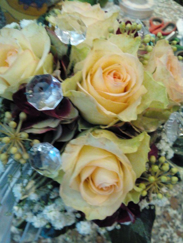 Due mani preparano dei fiori per un bouquet